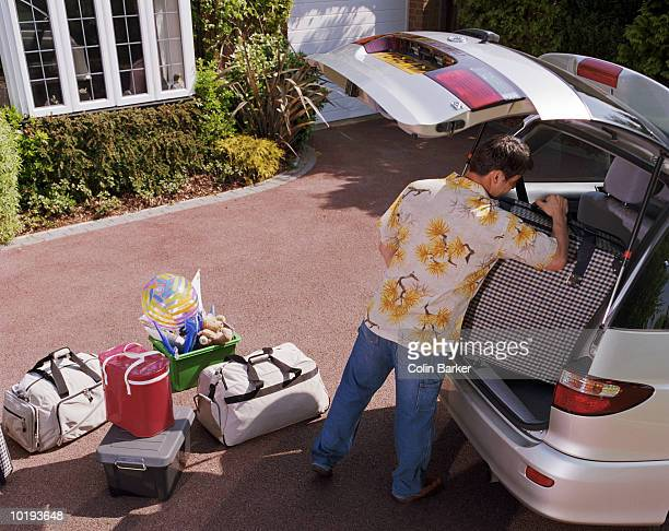 Man loading luggage into car on driveway, elevated view