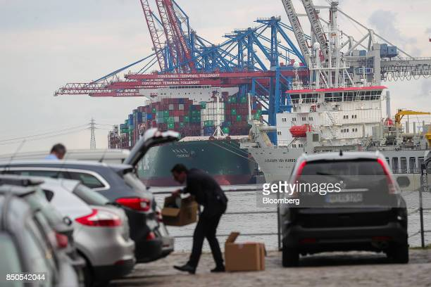 A man loads a box into the trunk of his automobile as shiptoshore cranes stand beside a container ship beyond at the HHLA Container Terminal...