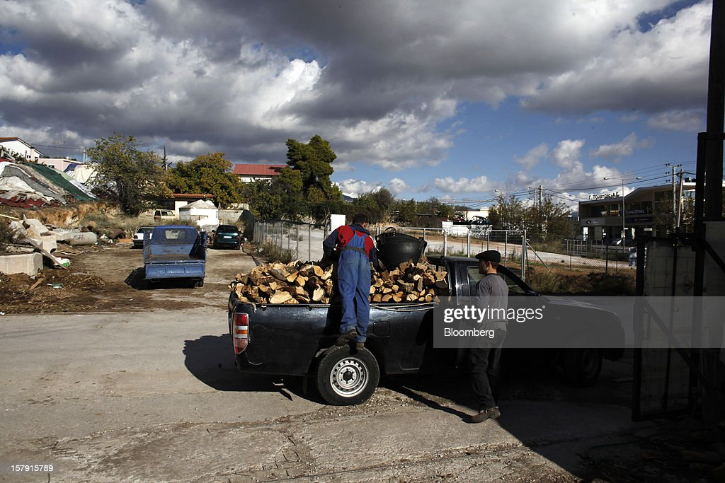 A man loads a pickup truck with logs of wood used for firewood from a supply store in Athens, Greece, on Friday, Dec. 7, 2012. Greece, the epicenter of Europe's debt crisis since revealing a bloated spending gap in late 2009, has faced regular demands to get a firmer grip on the budget or risk being forced out of the euro. Photographer: Kostas Tsironis/Bloomberg via Getty Images