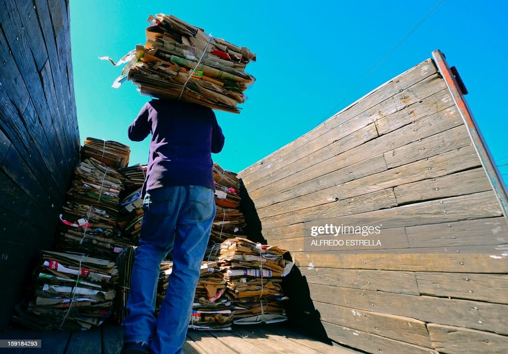 A man loads cardboard packs in a truck at the Recycling Center in Nezahualcoyotl, State of Mexico, on January, 09, 2013. AFP PHOTO/Alfredo Estrella