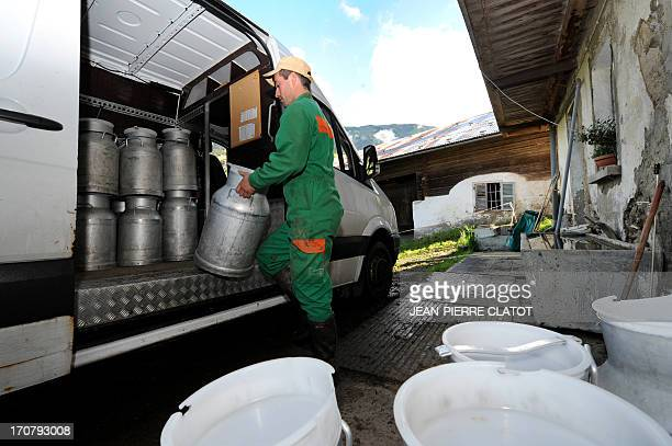 A man loads milk containers in a truck as part of a delivery to a Beaufort cheesemaking cooperative on June 11 2013 in Hauteluce Beaufort is a firm...