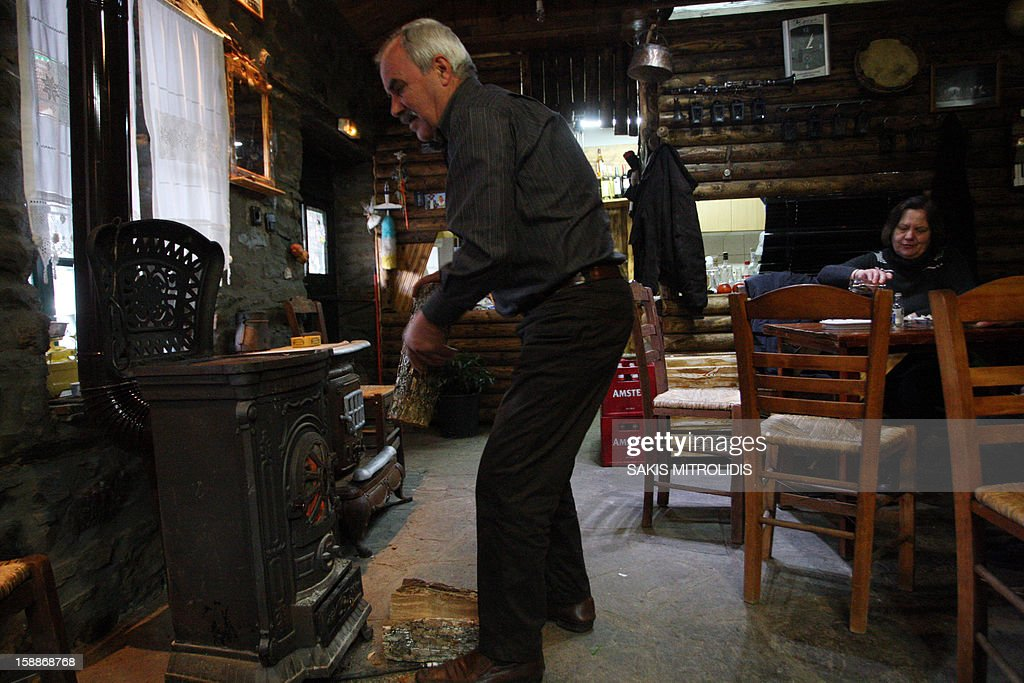 A man loads the wood stove of a cafe in Dotsiko, a village some 520km north of Athens, on 2 January, 2013. Air pollution in cities of Greece has surged in recent days because of people choosing wood over more expensive fuels to heat their homes in the grips of a continuing economic crisis. Illegal logging has surged also in Greece as Forest Authorities reported that illegal logging activities across the country accounts for up to 30 percent of all lost forestland. AFP PHOTO /Sakis Mitrolidis