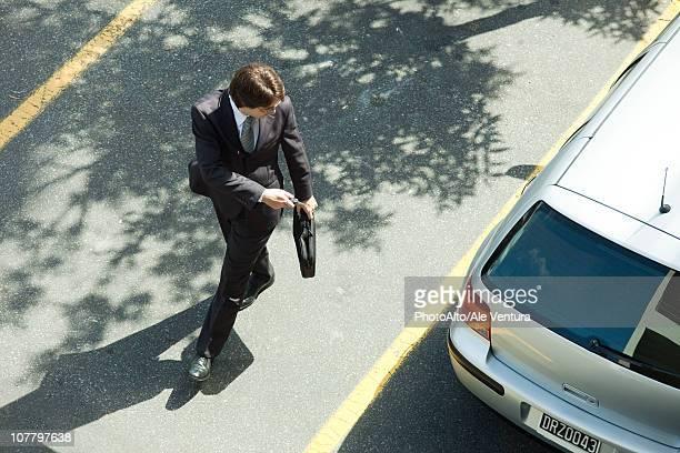 Man locking car doors using key remote as he walks away