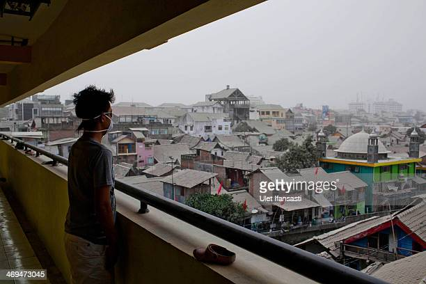 A man look at houses covered by ash from the eruptions of the Mount Kelud on February 15 2014 in Yogyakarta Indonesia More than 100000 people were...