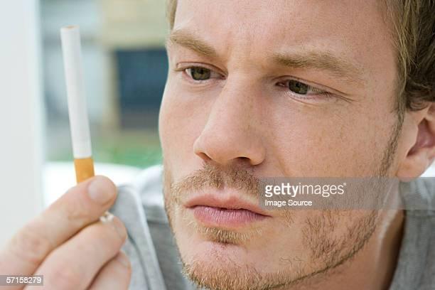 Hombre mirando a un cigarrillo