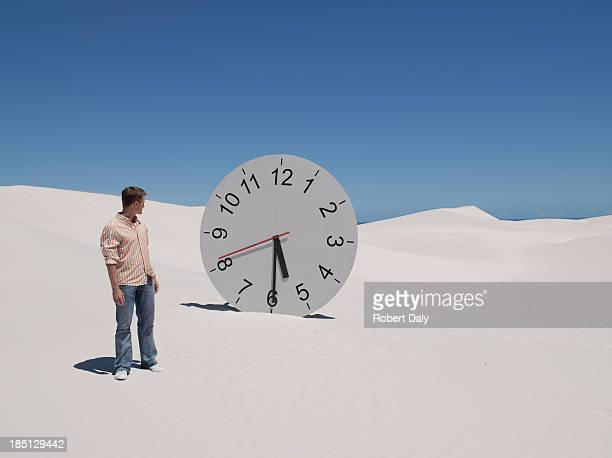A man looking at a clock in the desert