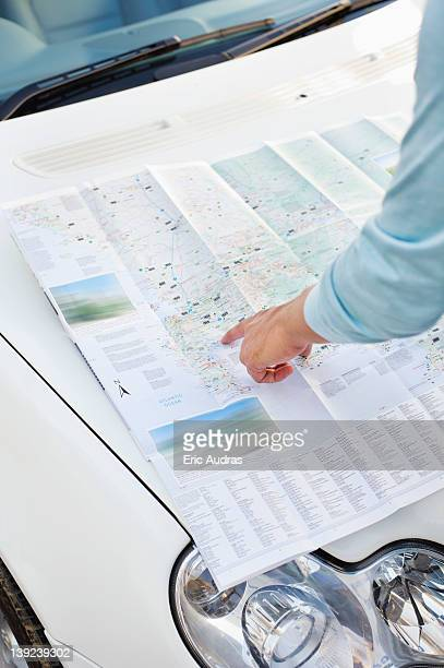 Man looking at a map on a car