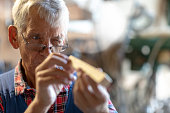 A senior man is squinting at a stick of wood. He's wearing glasses and a flannel shirt.