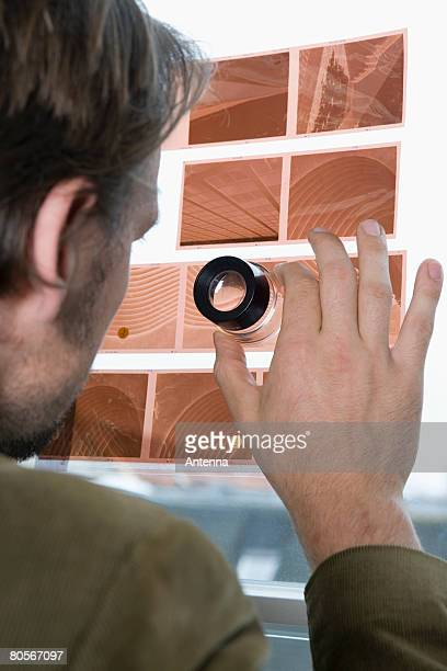 A man looking at a slide contact sheet