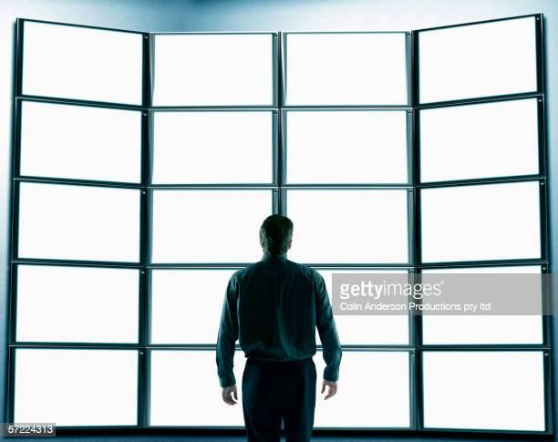 Man looking at a wall of flat screen monitors
