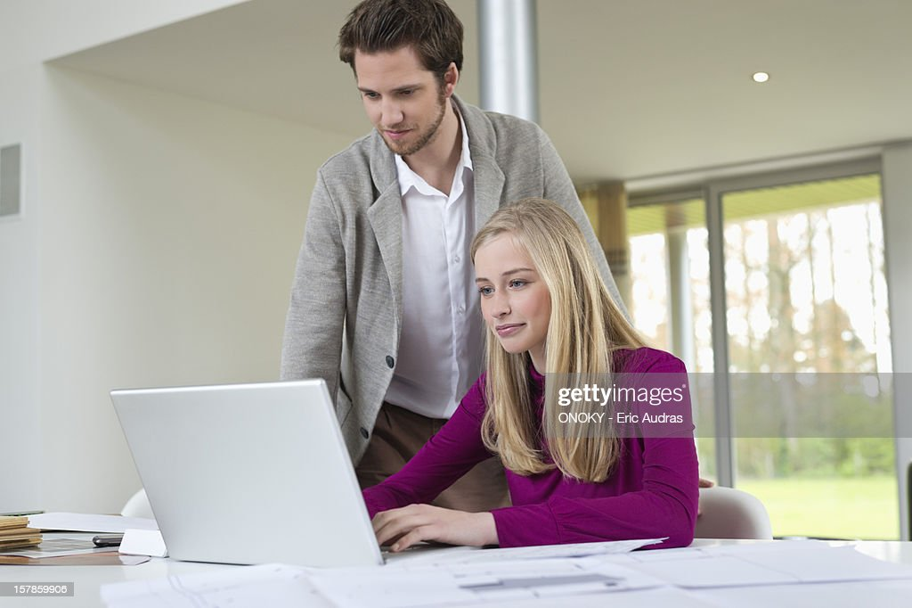 Man looking at a woman working on a laptop : Stock Photo
