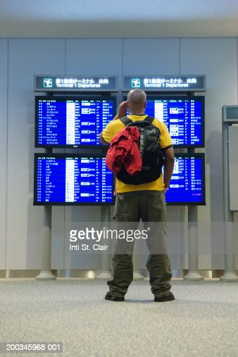 Man looking at arrival departure boards in airport, rear view