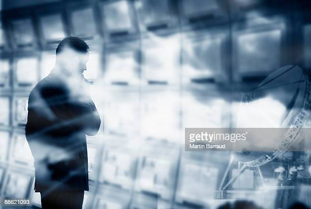 Man looking at bank of computer monitors