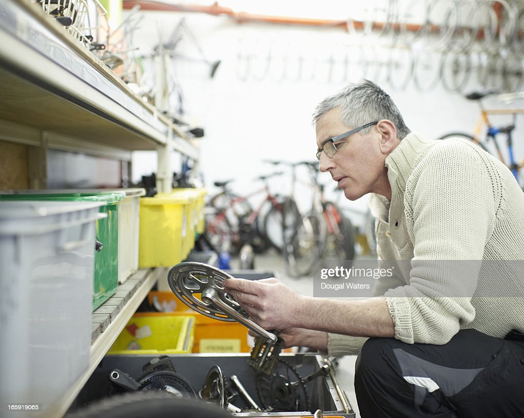 Man looking at bicycle parts in workshop. : Stock Photo