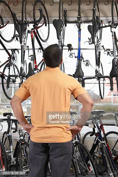 Man looking at bicycles in bicycle shop, hands on hips, rear view
