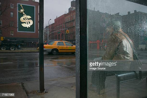 Man looking at billboard from bus shelter
