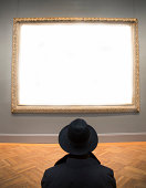 Man looking at blank framed canvas.\