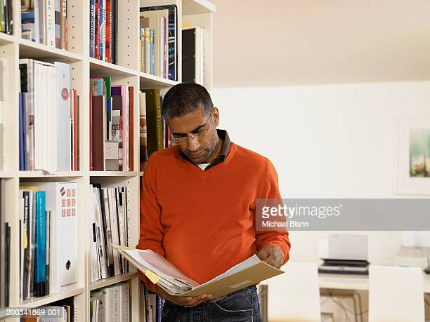 Man looking at book by bookshelf