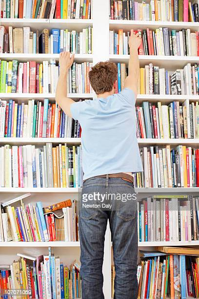 Man looking at bookcase, rear view