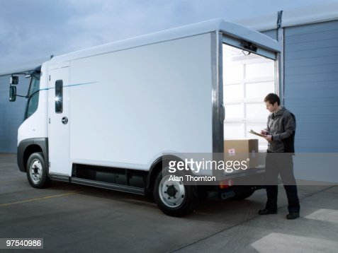 Man looking at box in back of electric van