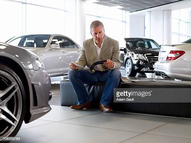 Man looking at brochure in automobile showroom