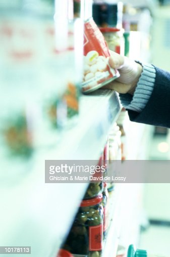 Man looking at can on supermarket shelf, close-up