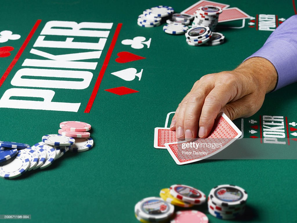 Man looking at cards at poker table, close-up of hand : Stock Photo