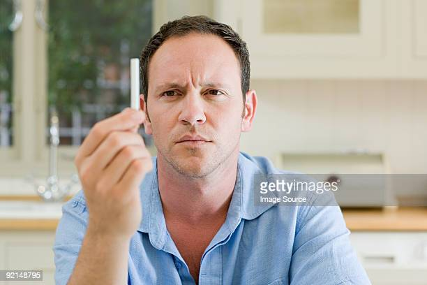 Man looking at cigarette