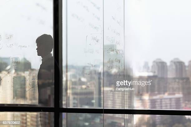 Man looking at city from window in business office