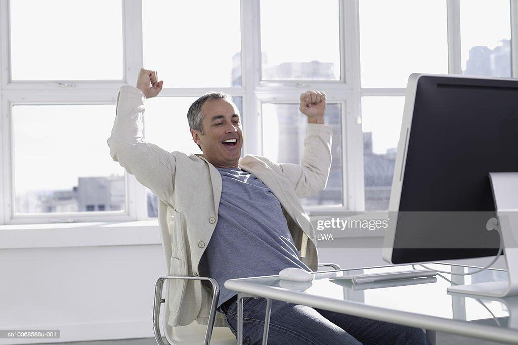 Man looking at computer, cheering : Stock Photo