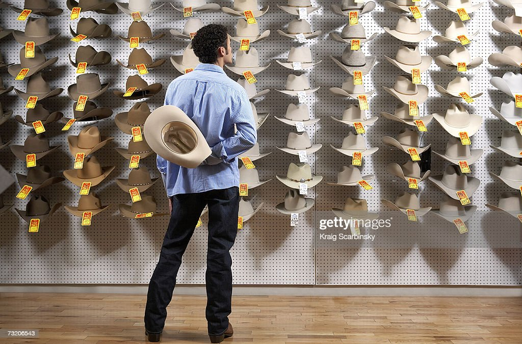 Man looking at cowboy hats in store, rear view : Stock Photo