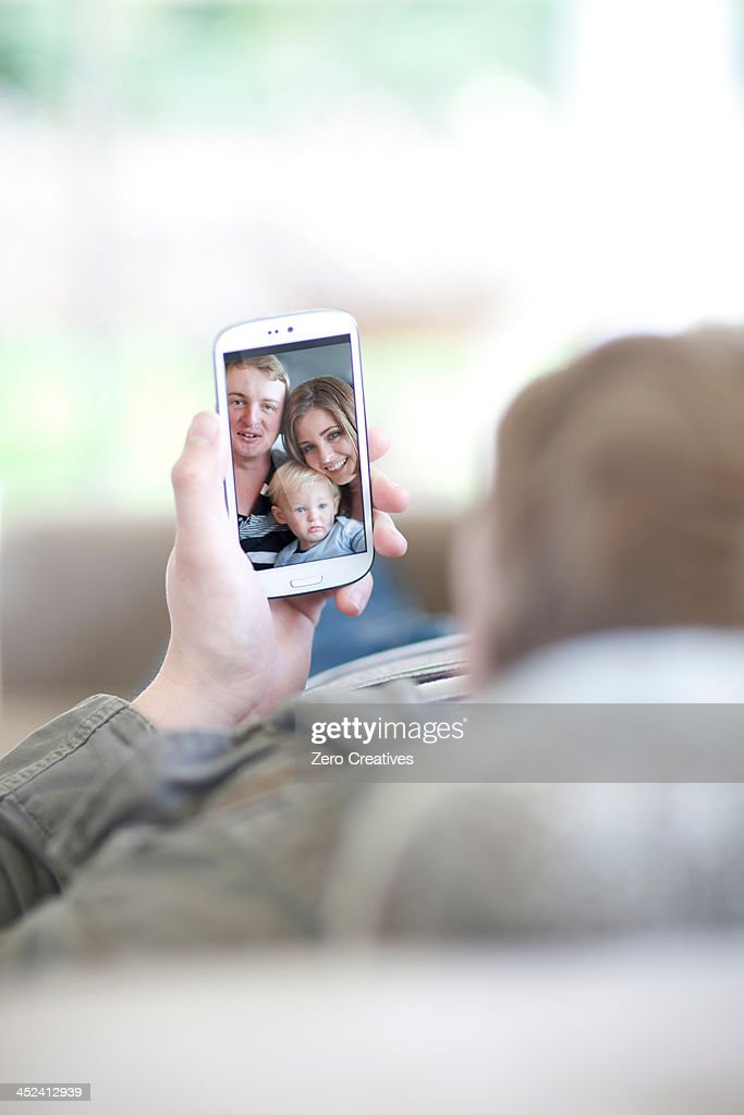 Man looking at family photo on cellphone