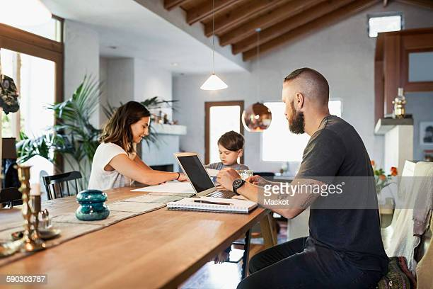 Man looking at family while working at dining table in house