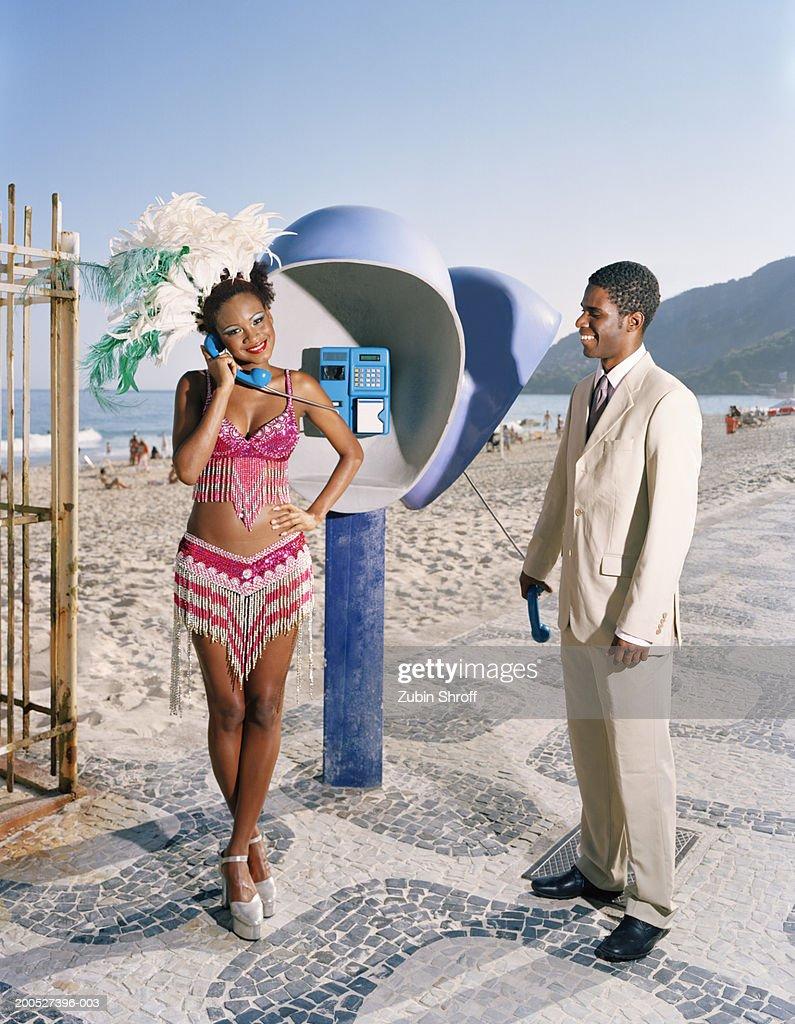 Man looking at female carnival dancer using pay phone at beach : Stock Photo
