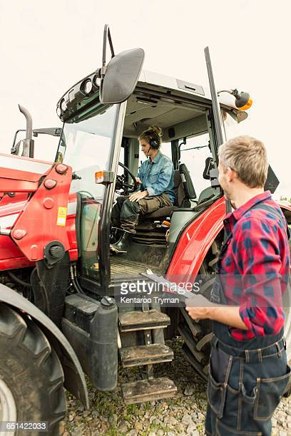 Man looking at female worker driving tractor in farm