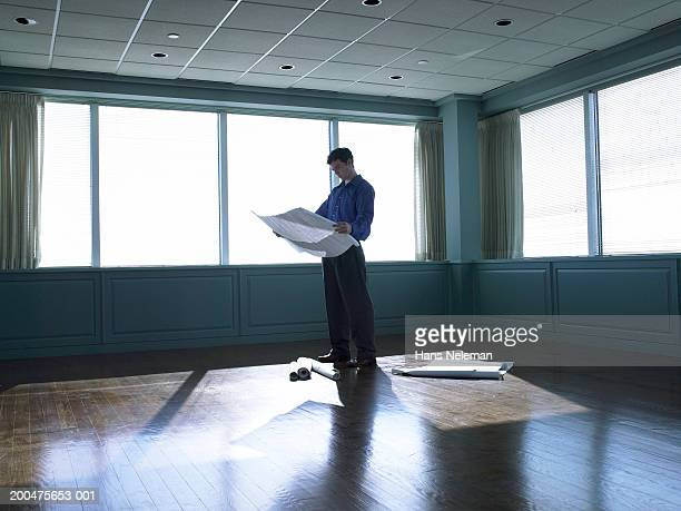Man looking at floor plans in empty office space