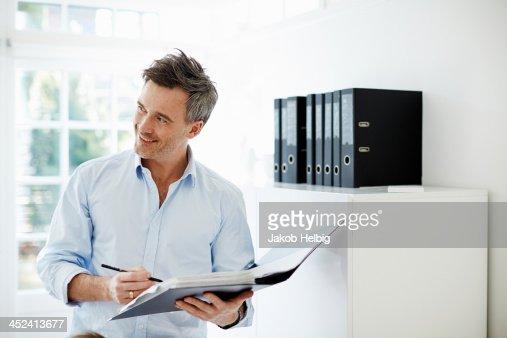 Man looking at folder of paperwork