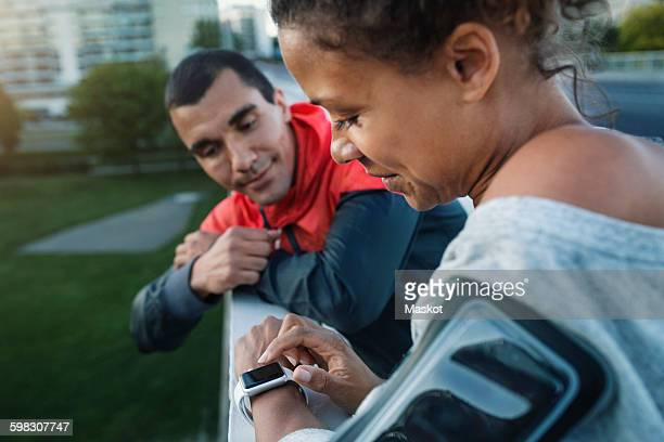 Man looking at friend using smart watch while standing by railing at sidewalk