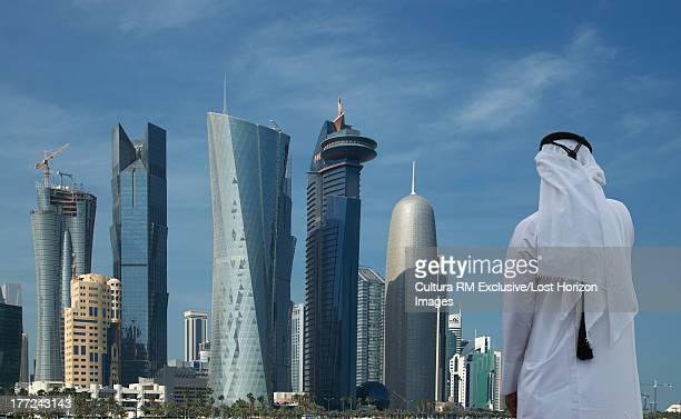 Man looking at futuristic skyscrapers of downtown Doha, Qatar