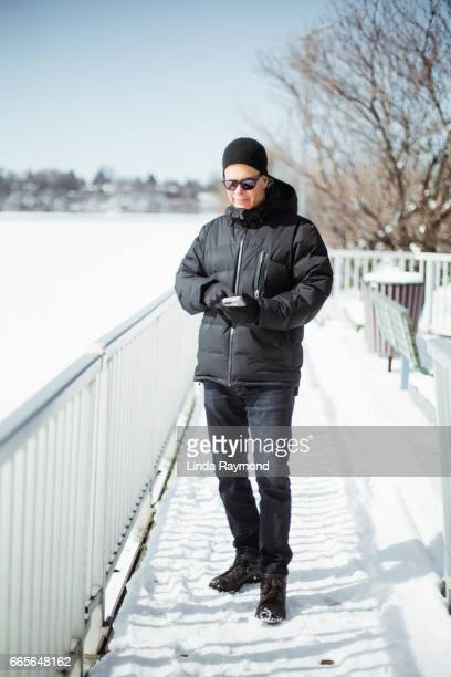 A man looking at gis cellphone at winter