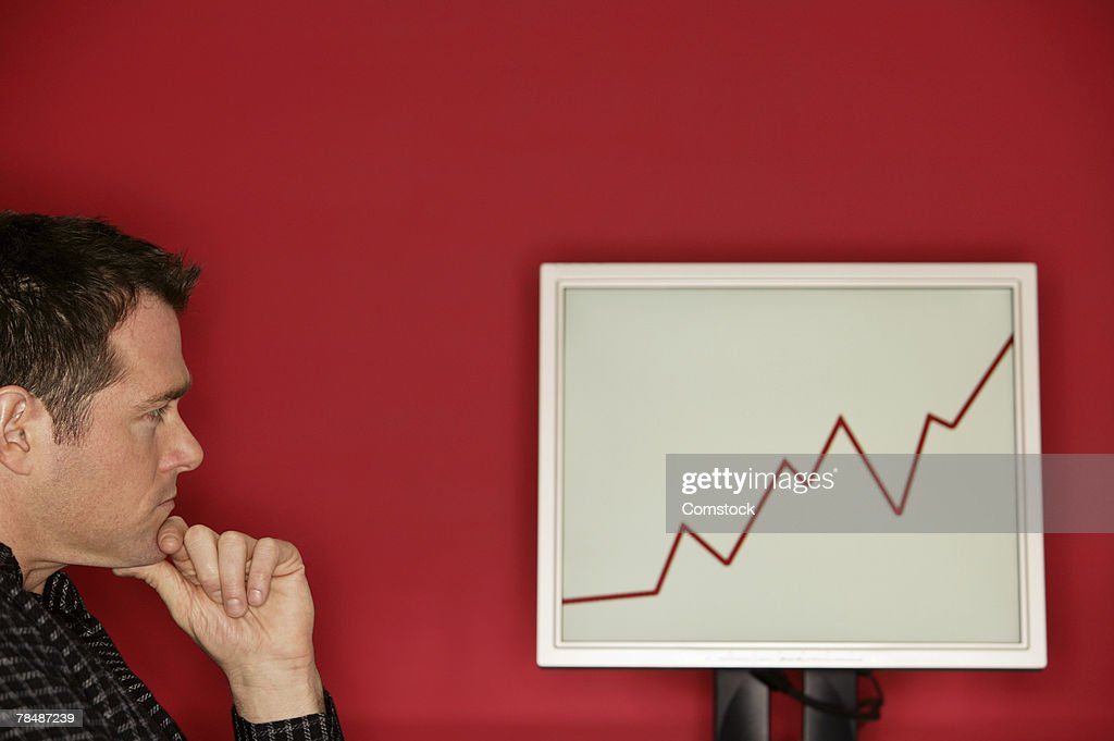 Man looking at graph on a monitor : Stock Photo
