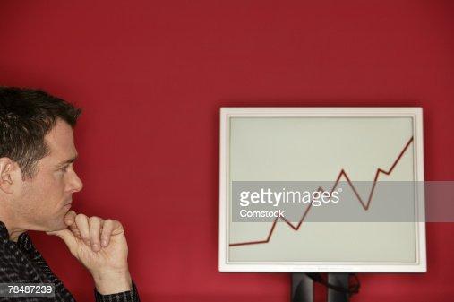 Man looking at graph on a monitor : Stock Photo
