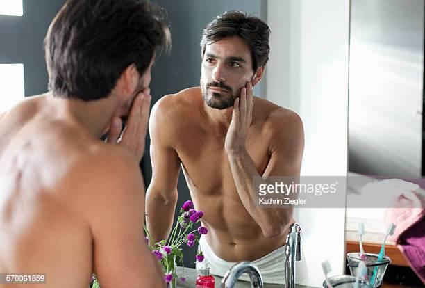 man looking at himself in bathroom mirror