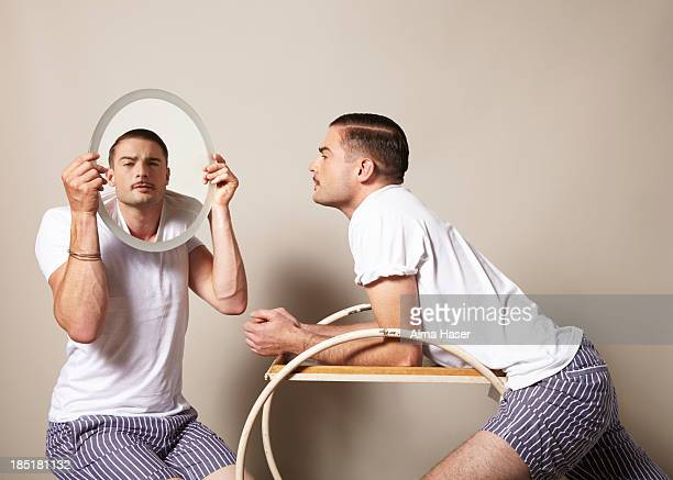 Man looking at himself in the mirror held by a boy