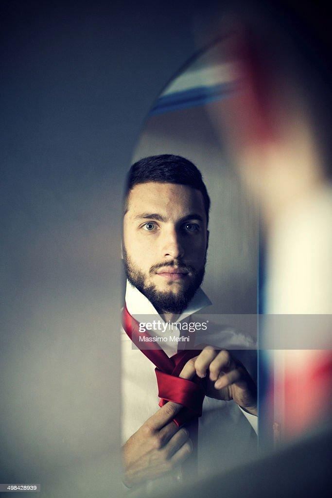 Man looking at himself wearing tie in the mirror