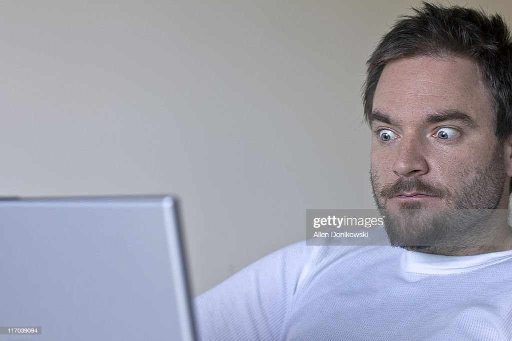 Man looking at his laptop screen : Stock Photo