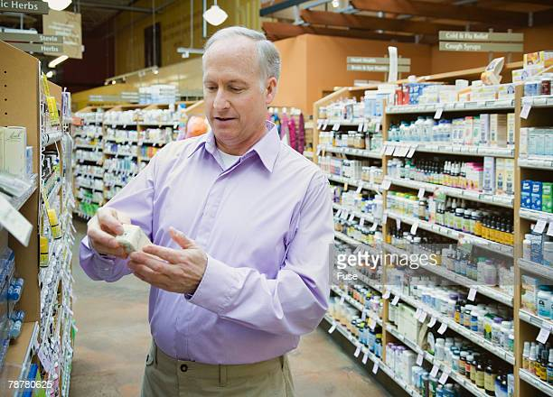 Man Looking at Homeopathic Medicines in Health Food Store