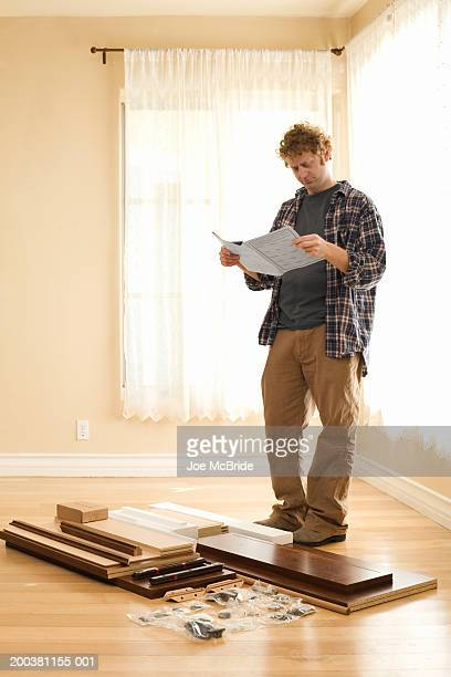 Man looking at instructions, unassembled furniture on floor