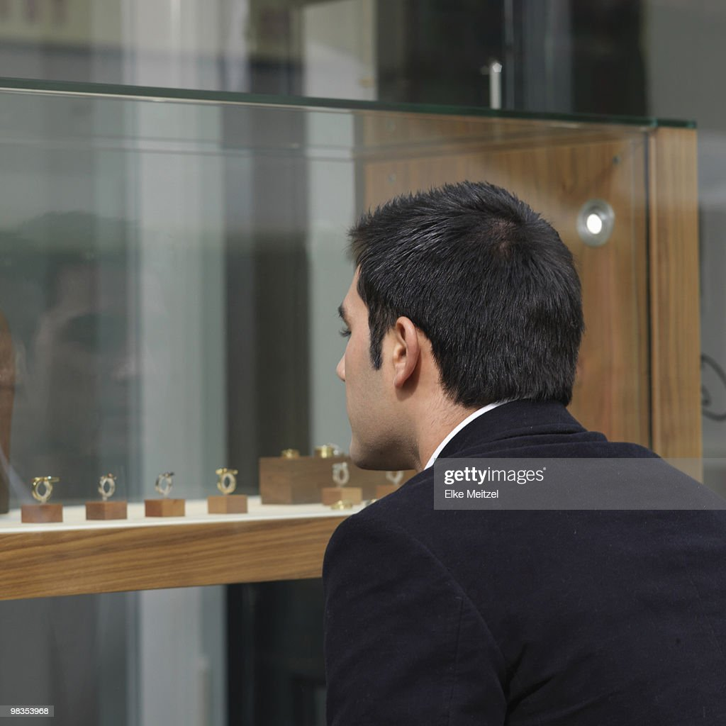 man looking at jewelry in shop window