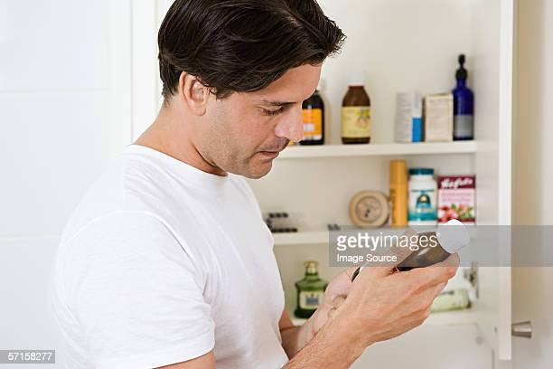 Man looking at label on cough medicine